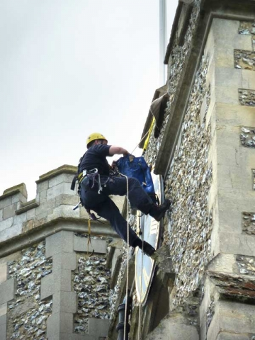 workmen abseiling down the clock tower
